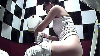 Brunette lovely woman in white pants pisses in the public toilet