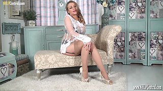 Pretty all natural busty blonde Penny Lee shows it all off as she teases in her tan nylons