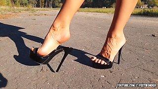 Walking in black high heeled mules