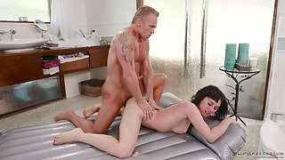 Attractive brunet masseuse Olive Glass gives a nuru massage to one tattooed man