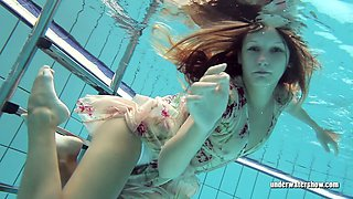Redhead doll Lucy Gurchenko swimming in a pool