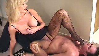 Fetish blonde in sexy stockings is trampling and making dude suck her feet
