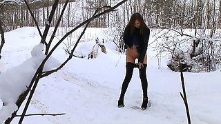 Fine brunette student girl in the winter forest pisses on the snow